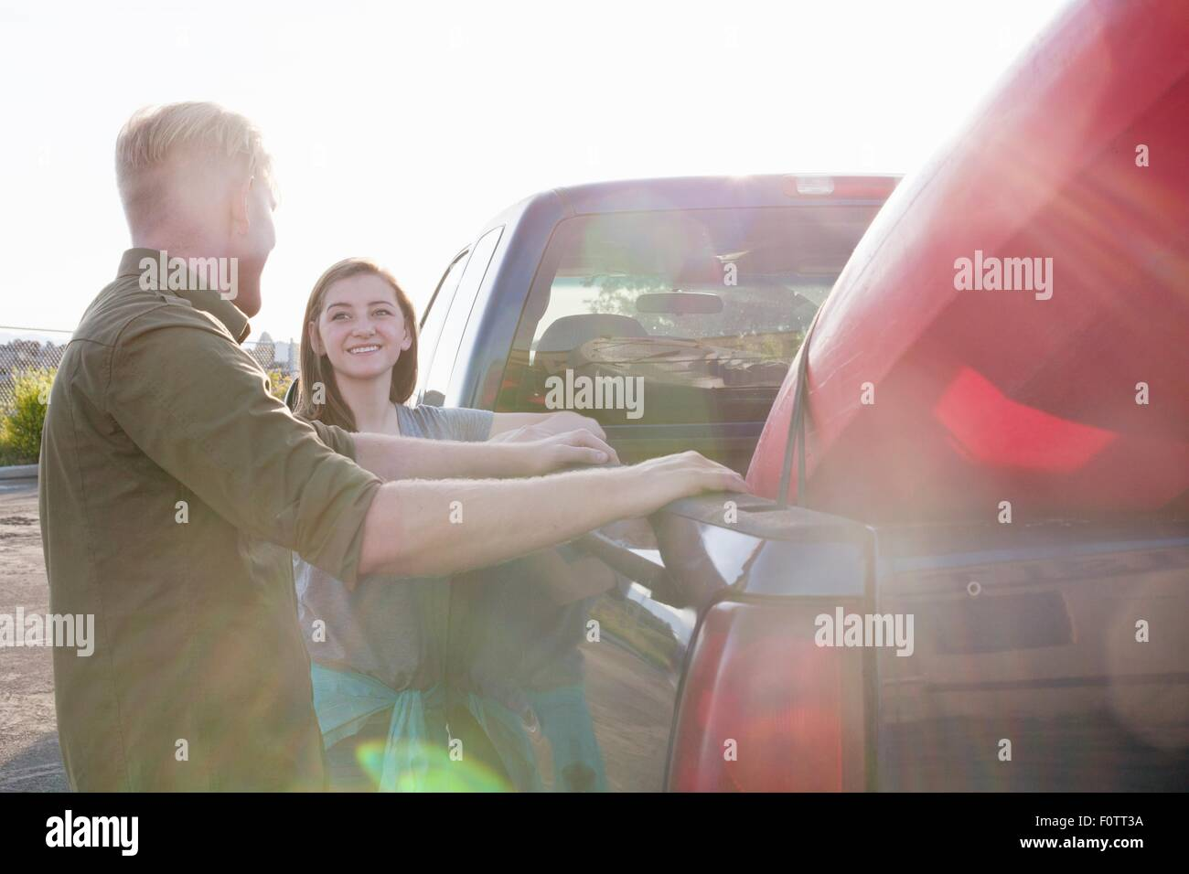 Young couple leaning against pick up truck, looking at each other smiling, lens flare - Stock Image