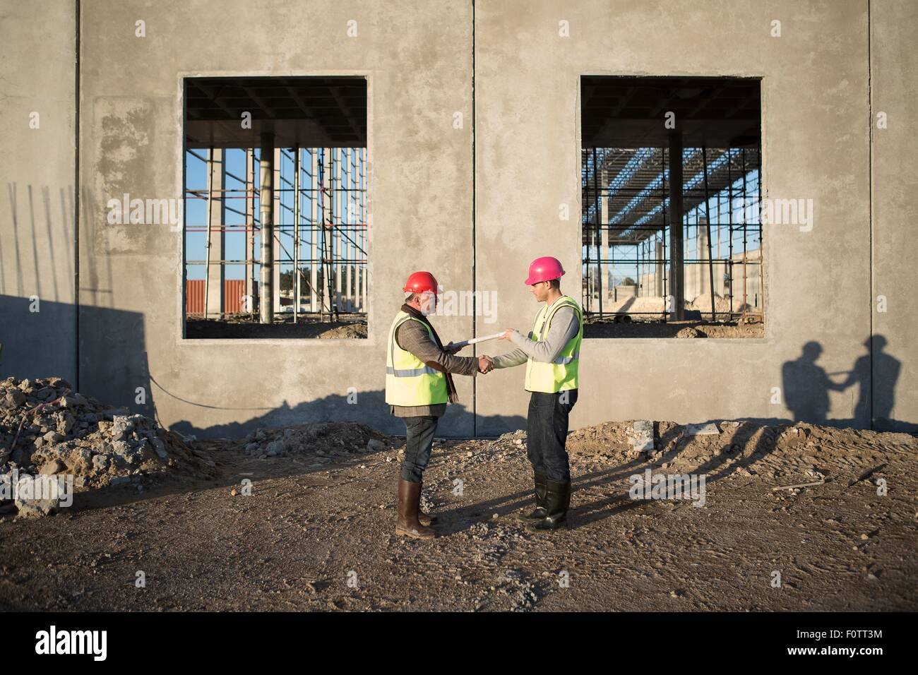 Architect and surveyor handing over blueprint on construction site architect and surveyor handing over blueprint on construction site malvernweather Images