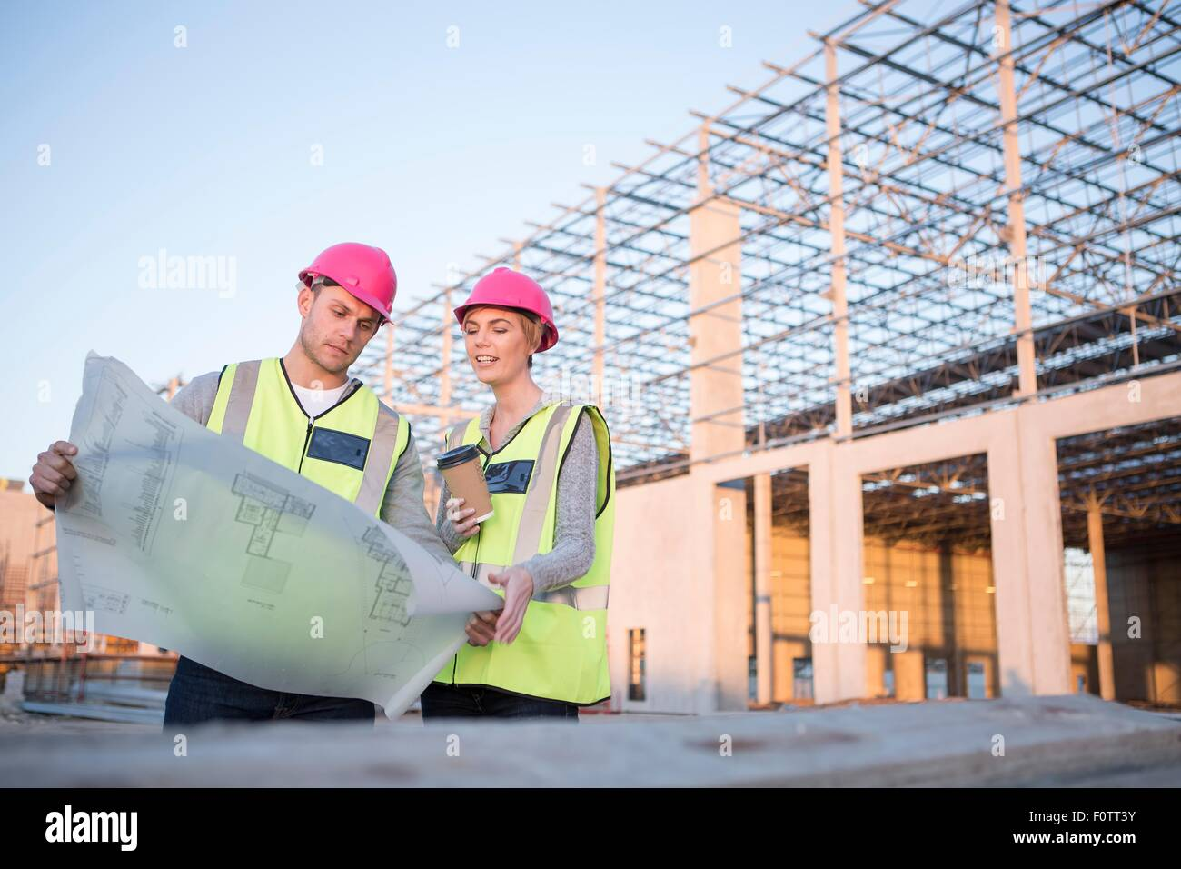 Builder And Architect Looking At Blueprint On Construction Site