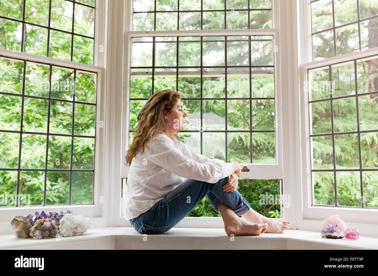 Portrait of mature woman sitting on living room windowsill looking out of window - Stock Image