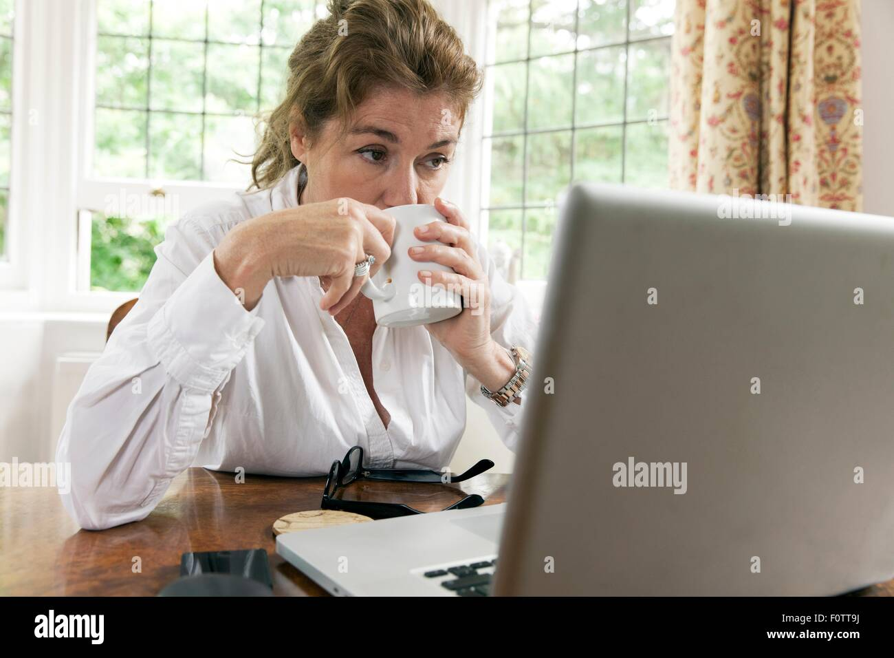 Worried mature woman working on laptop whilst drinking coffee in living room - Stock Image