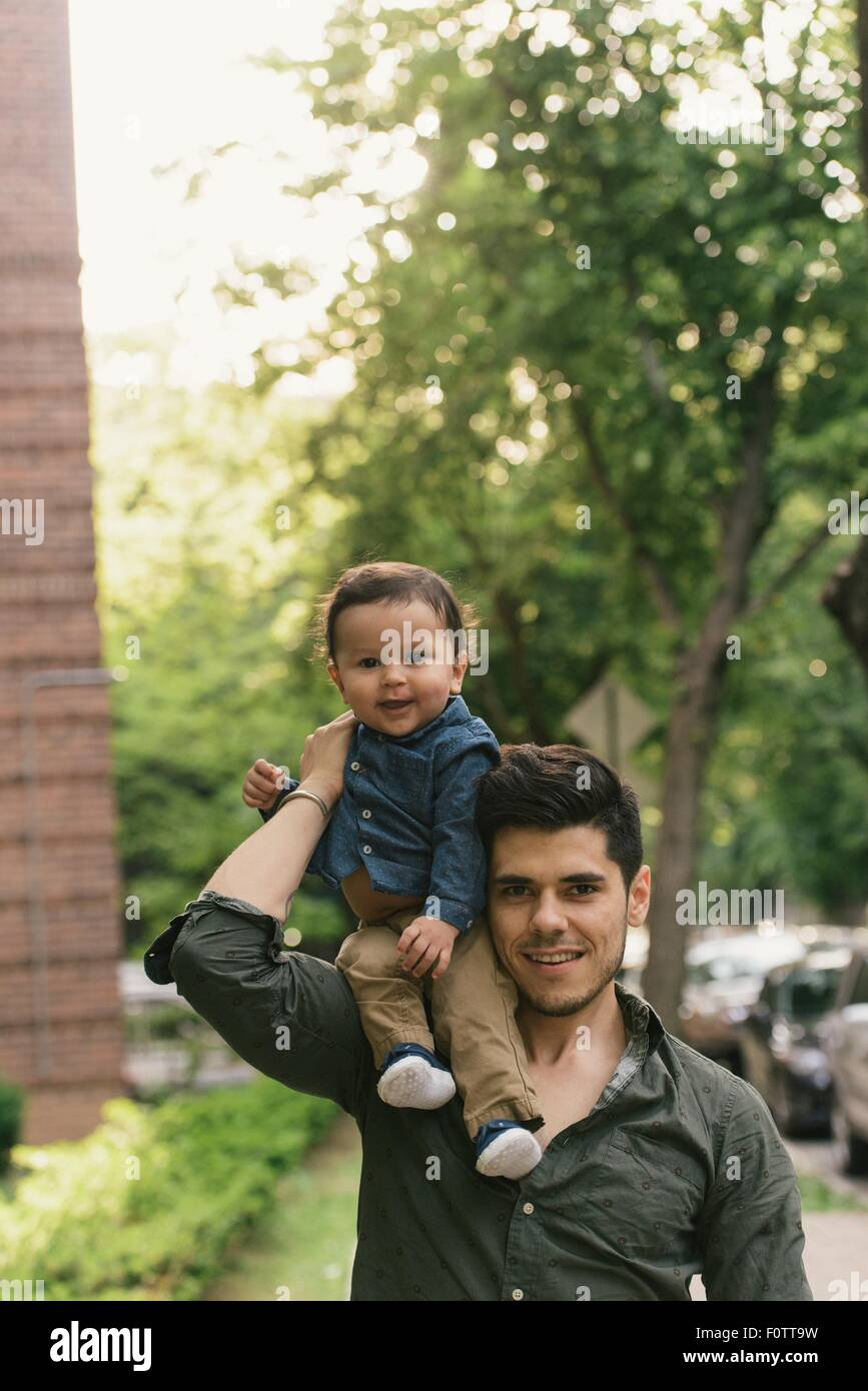 Baby boy sitting on fathers shoulder, looking at camera smiling - Stock Image