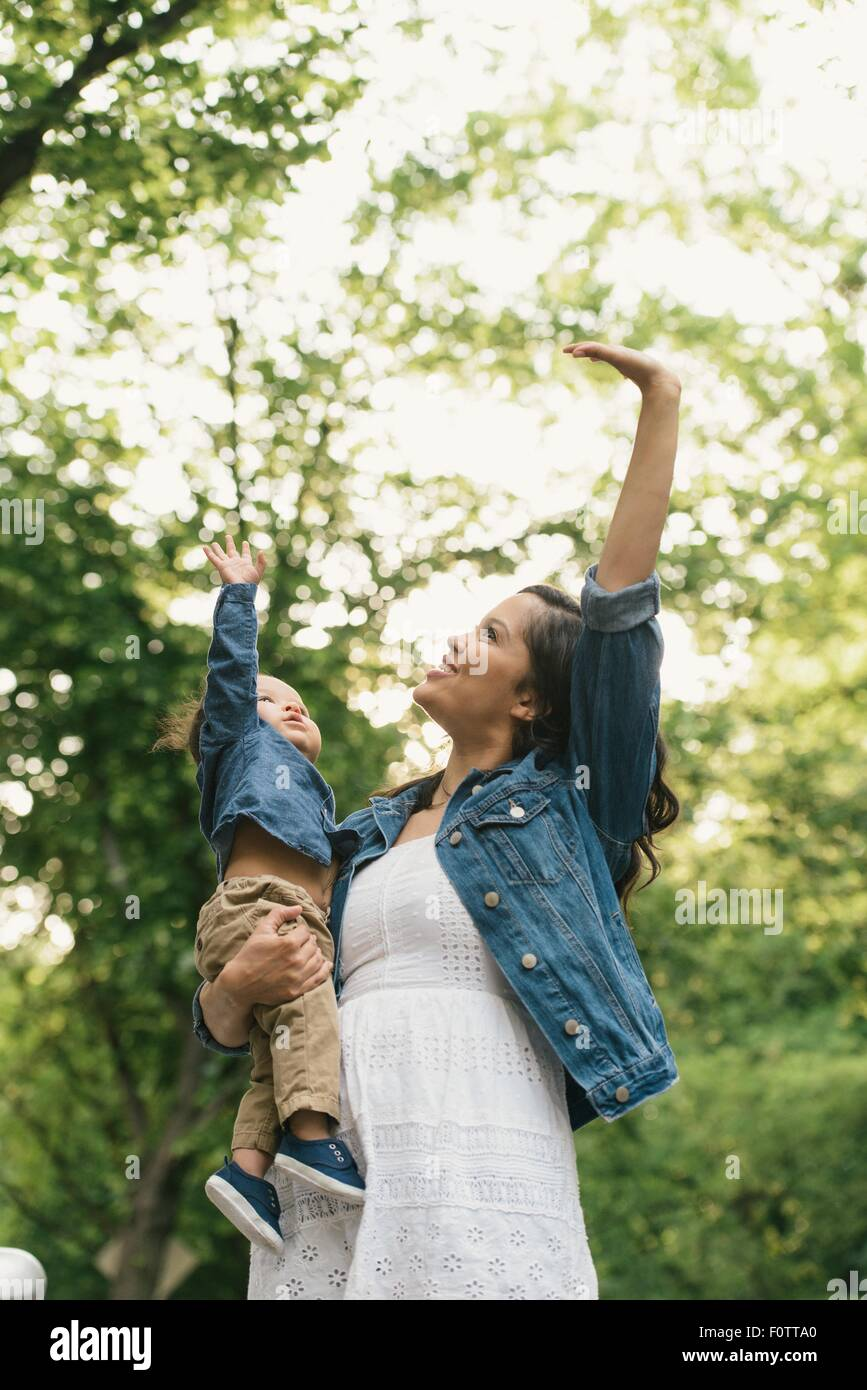 Low angle view of mother standing carrying baby boy, reaching up - Stock Image