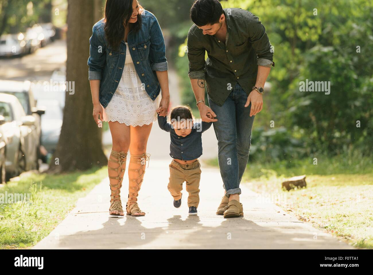 Front angle view of mother and father holding baby boys hands while walking - Stock Image