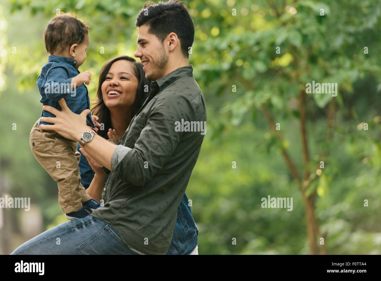 Side view of mother and father supporting baby boy to stand - Stock Image