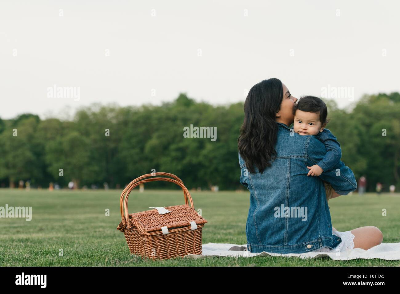 Rear view of mother sitting by picnic basket holding baby boy - Stock Image