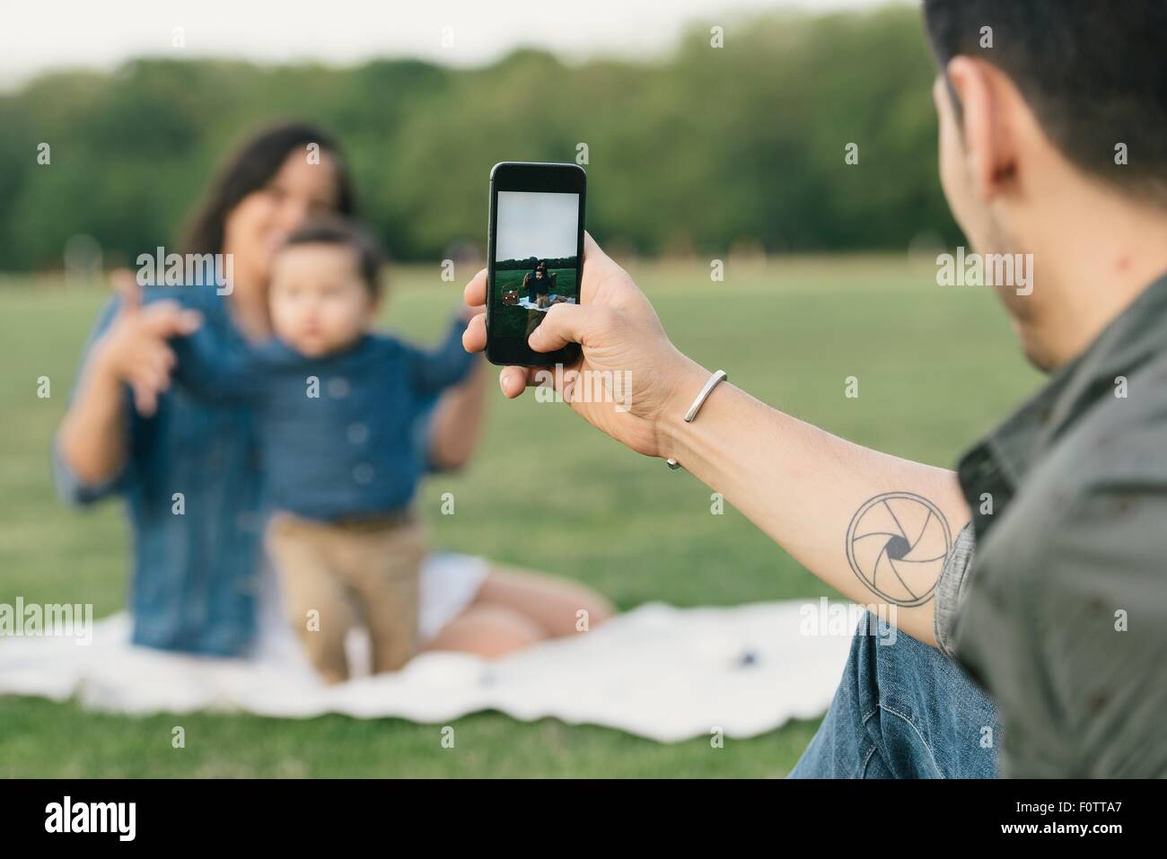 Young man using smartphone to take photograph of family - Stock Image