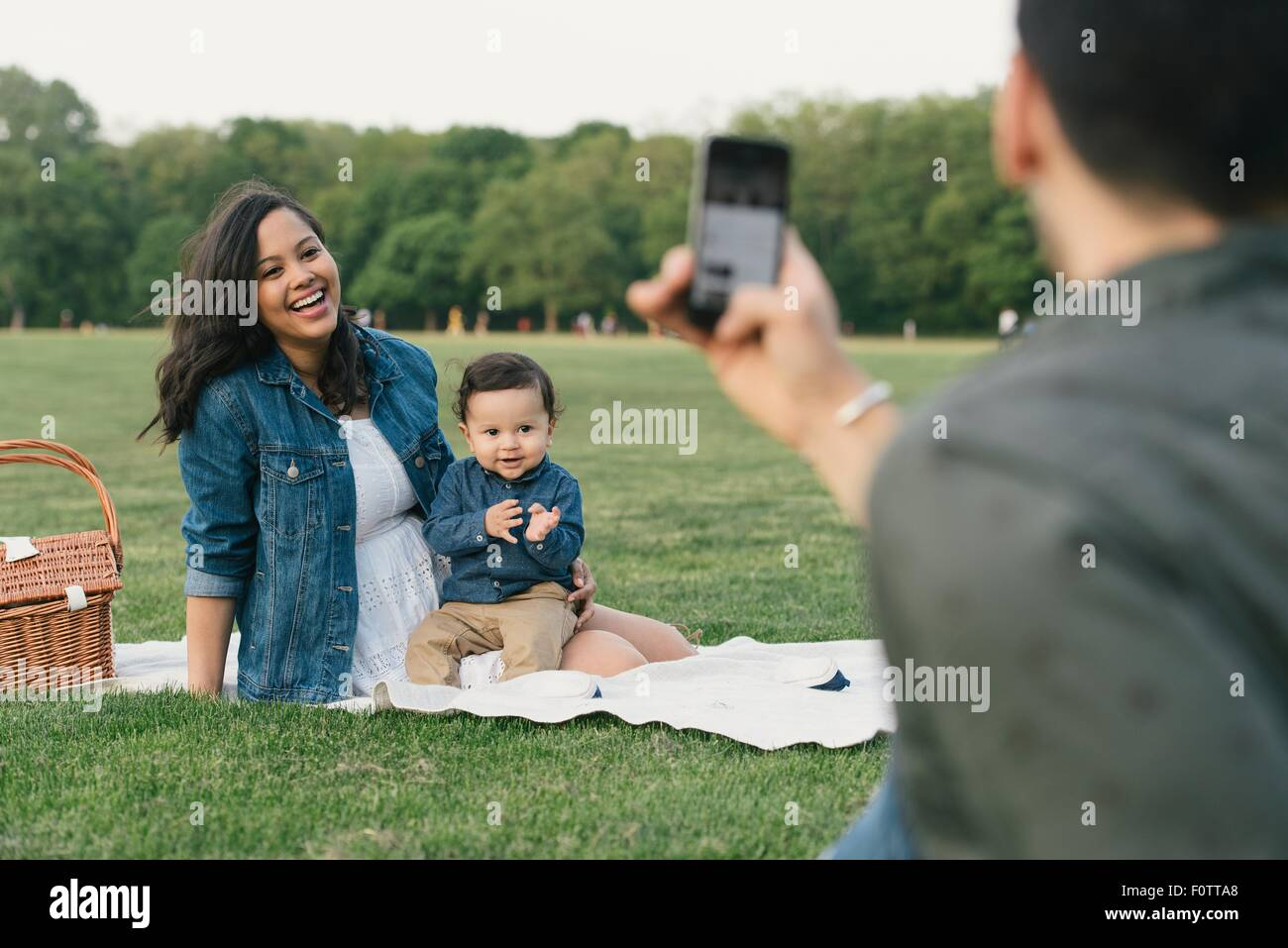 Young man using smartphone to take photograph of smiling family - Stock Image