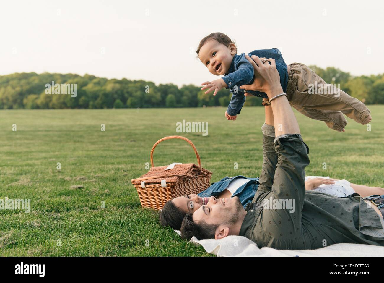 Mother and father laying on backs raising baby boy into the air - Stock Image