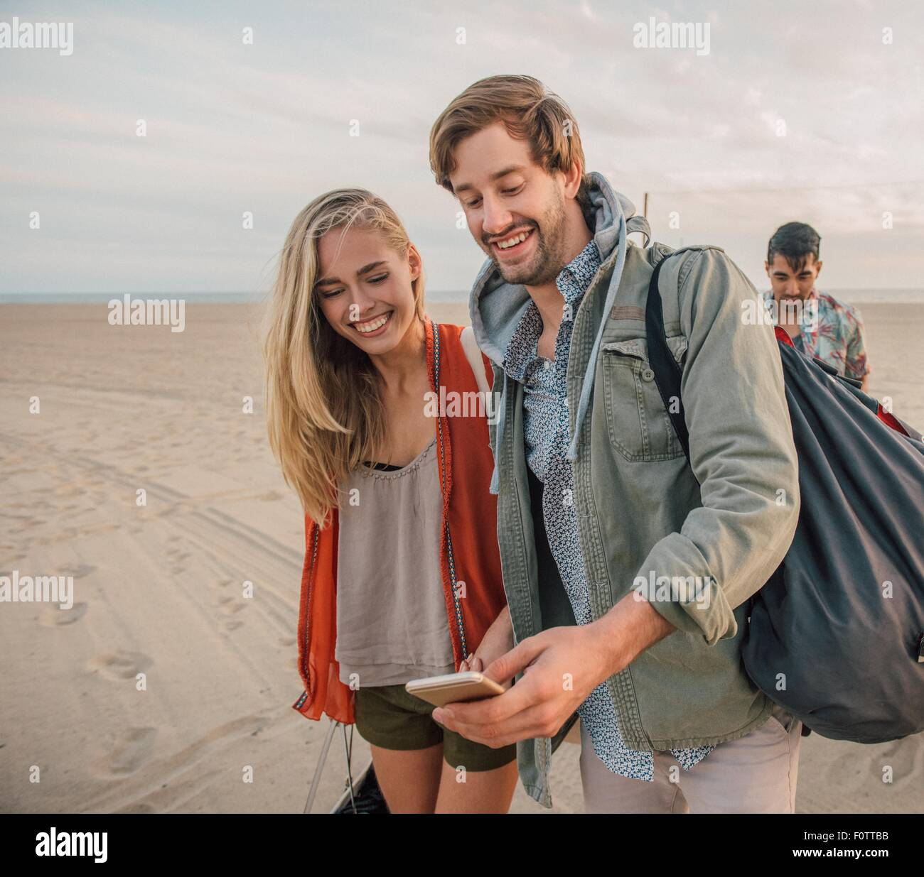 Group of friends walking along beach, young couple looking at smartphone Stock Photo