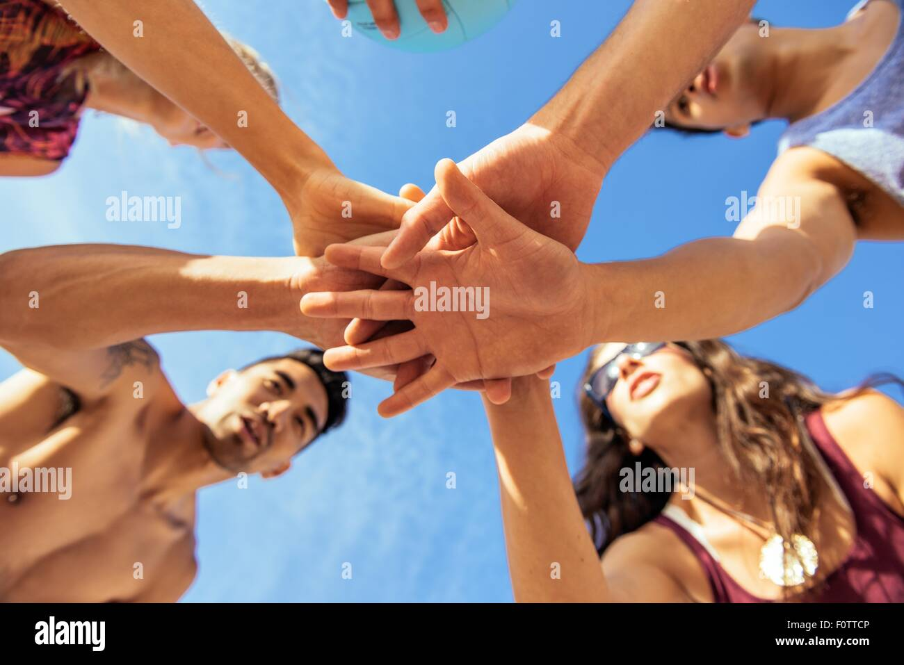Group of friends joining hands on beach, low angle view - Stock Image
