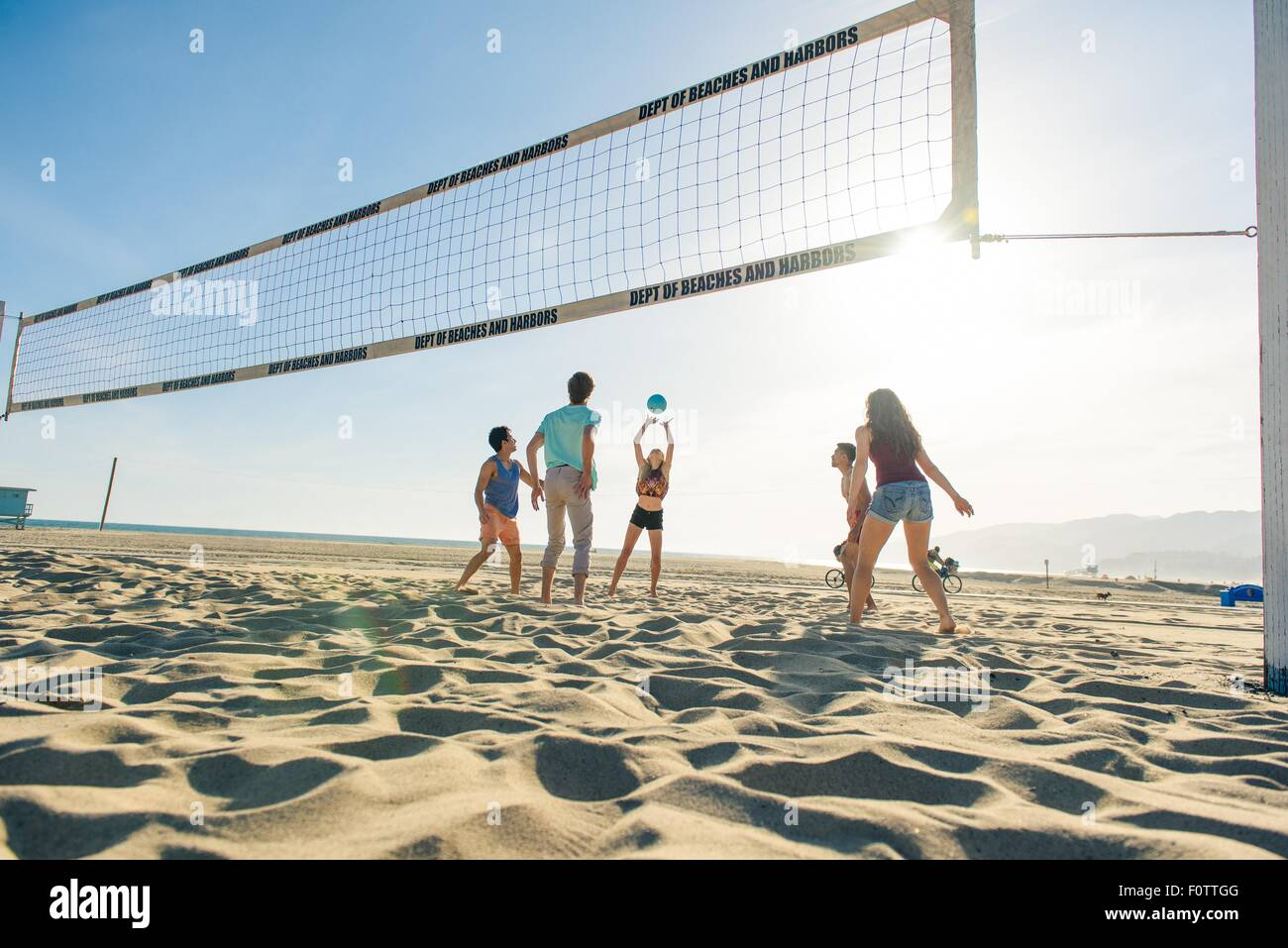 Group of friends playing volleyball on beach - Stock Image