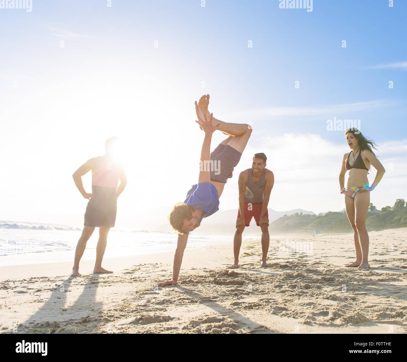 Group of friends on beach watching friend do handstand - Stock Image