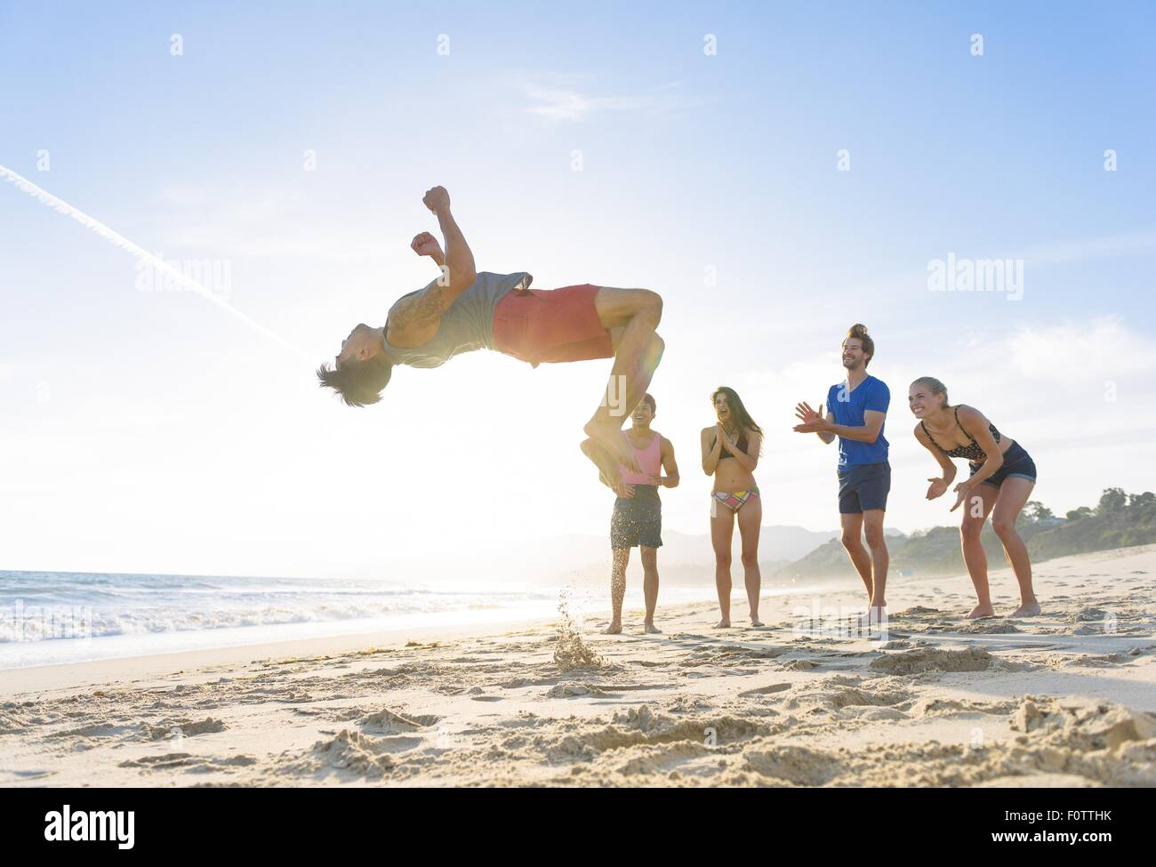 Group of friends on beach watching friend do somersault - Stock Image