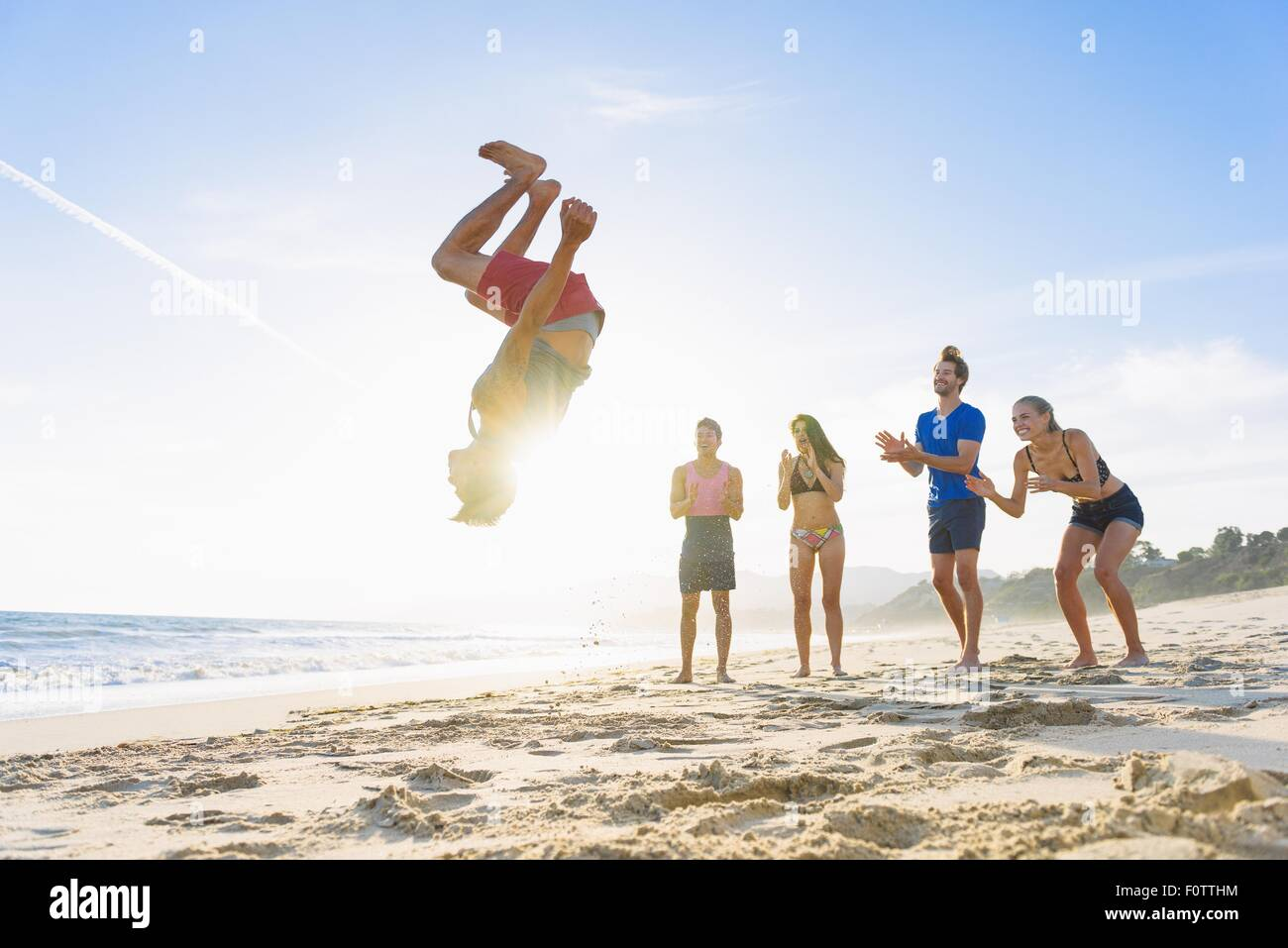 Group of friends on beach watching friend do somersault Stock Photo