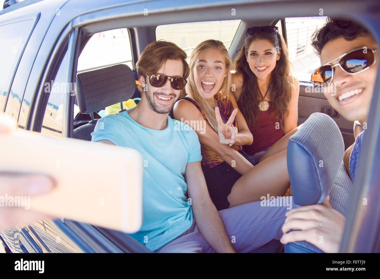 Group of friends sitting in car, taking self portrait with smartphone, laughing - Stock Image