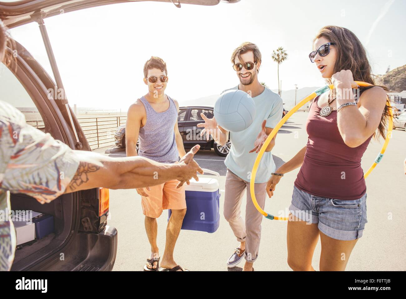 Group of friends standing by car, holding picnic and play items - Stock Image