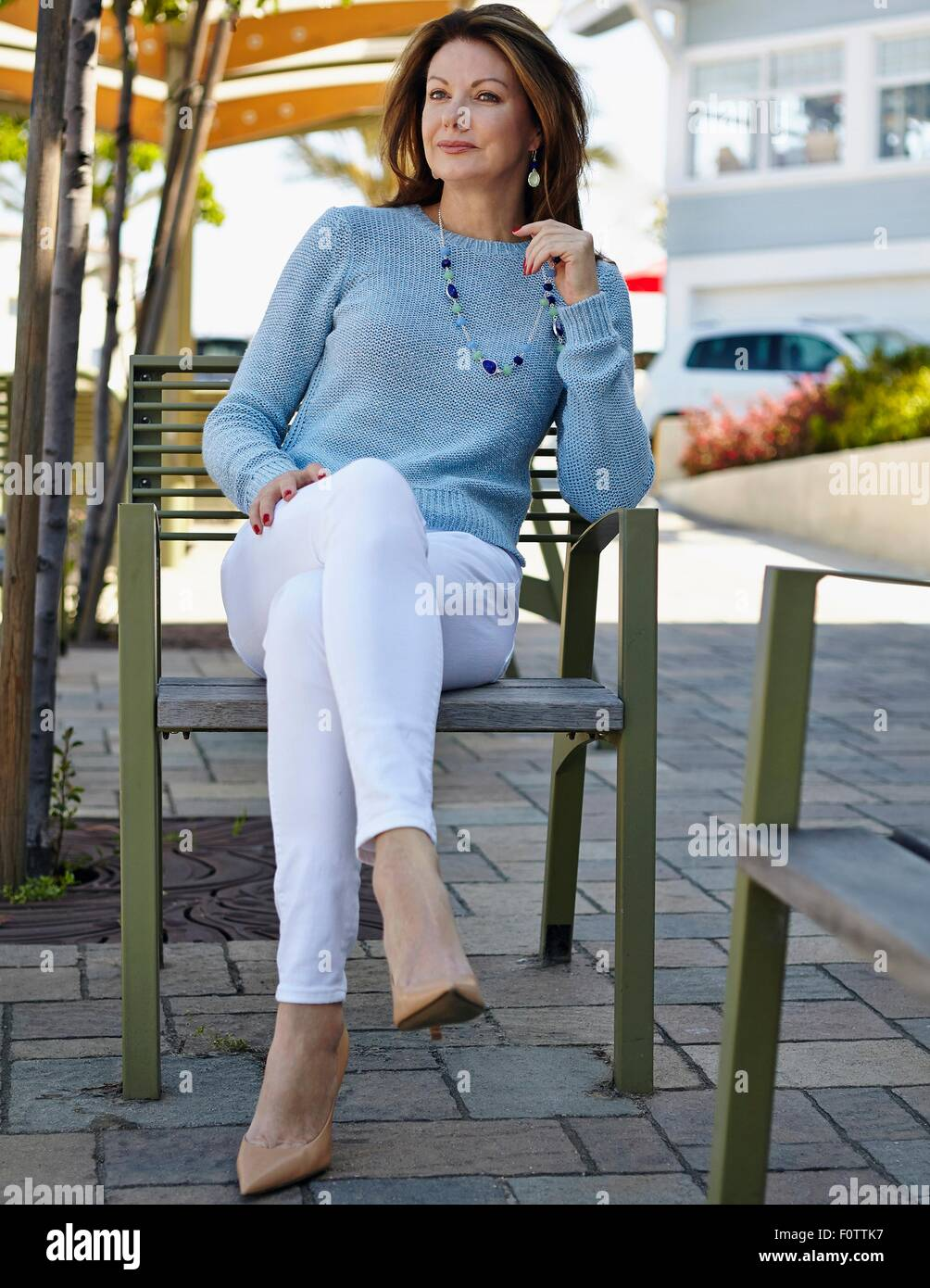 Portrait of elegant mature woman sitting on patio chair - Stock Image