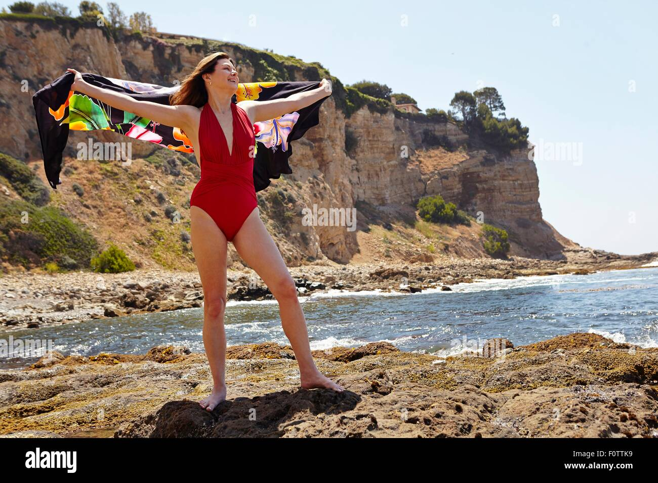 Portrait of mature woman wearing red bathing costume posing with sarong at coast - Stock Image
