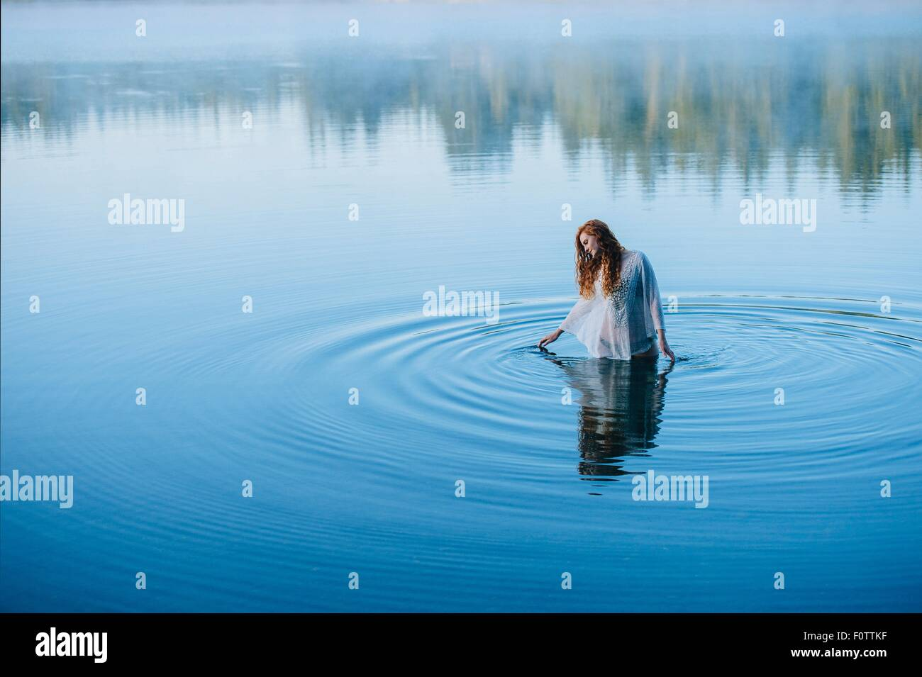 Young woman standing in middle of lake ripples looking down - Stock Image