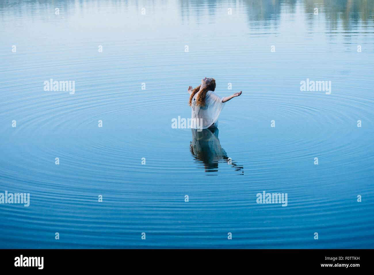 Young woman standing in middle of lake ripples with arms open and head back - Stock Image