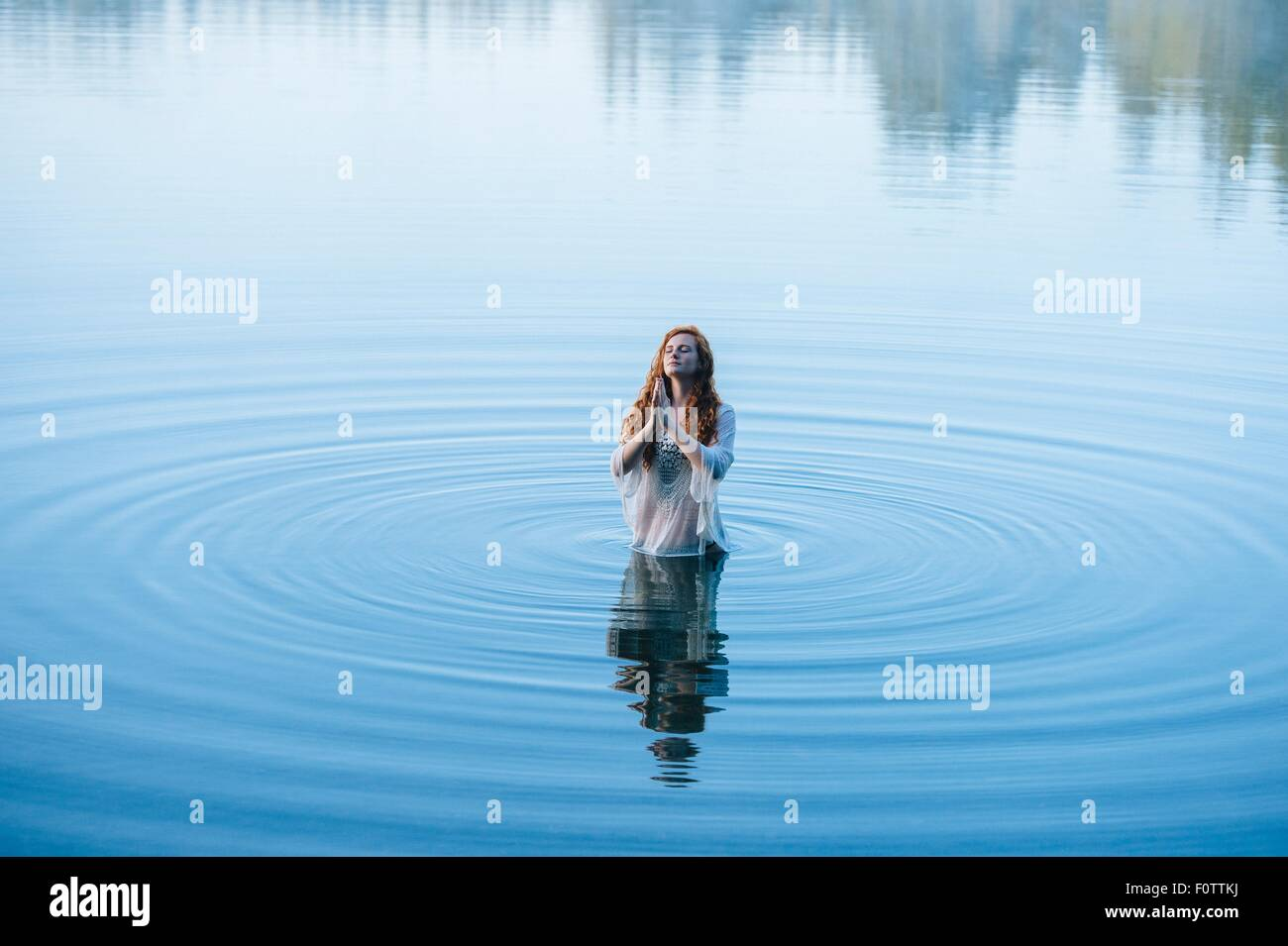 Young woman standing in lake ripples praying with eyes closed - Stock Image