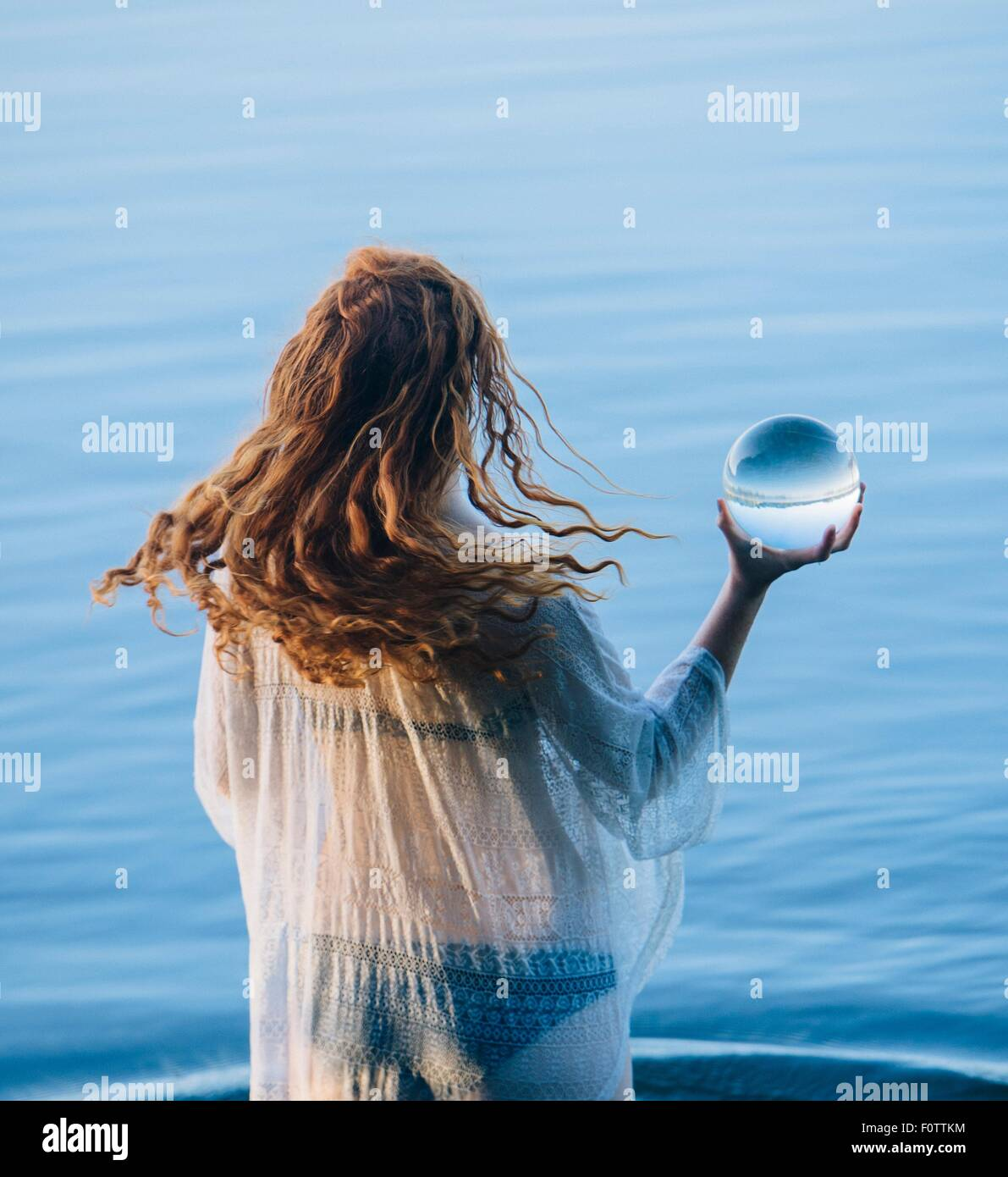 Rear view of young woman with long red hair standing in lake holding crystal ball - Stock Image
