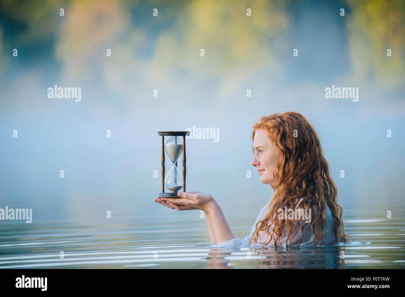 Young woman standing in misty lake gazing at hourglass - Stock Image