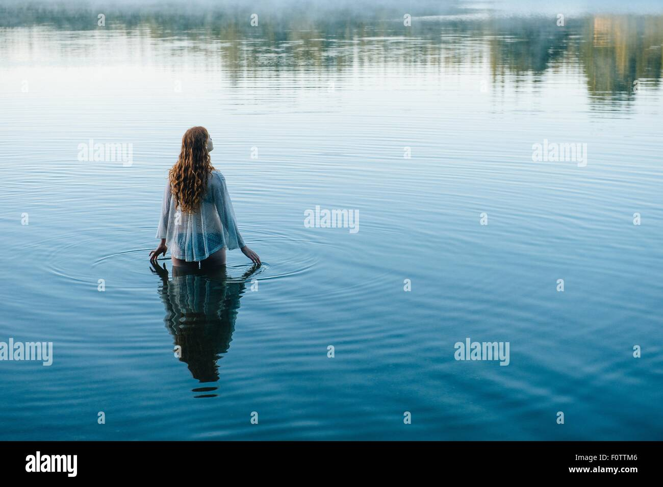 Rear view of young woman in lake rippling surface with her fingers - Stock Image