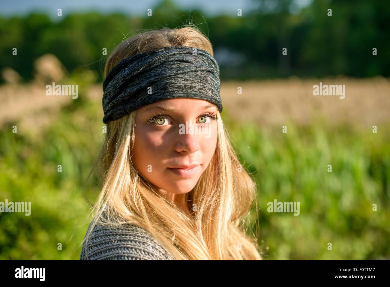 Portrait of pretty young woman with green eyes wearing bandana - Stock Image