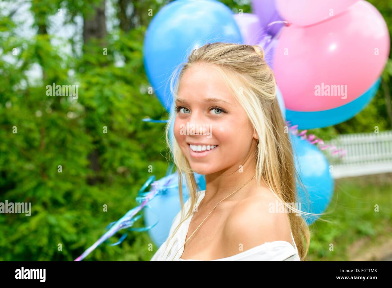 Portrait of pretty young woman with long blond hair holding bunch of balloons - Stock Image