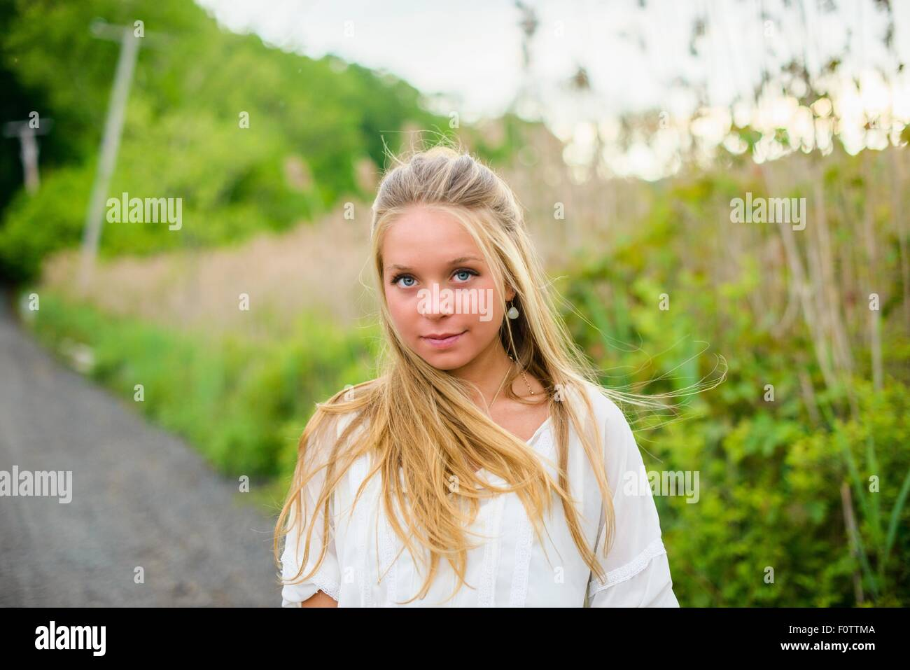 Portrait of  young woman with long blond hair on rural road - Stock Image