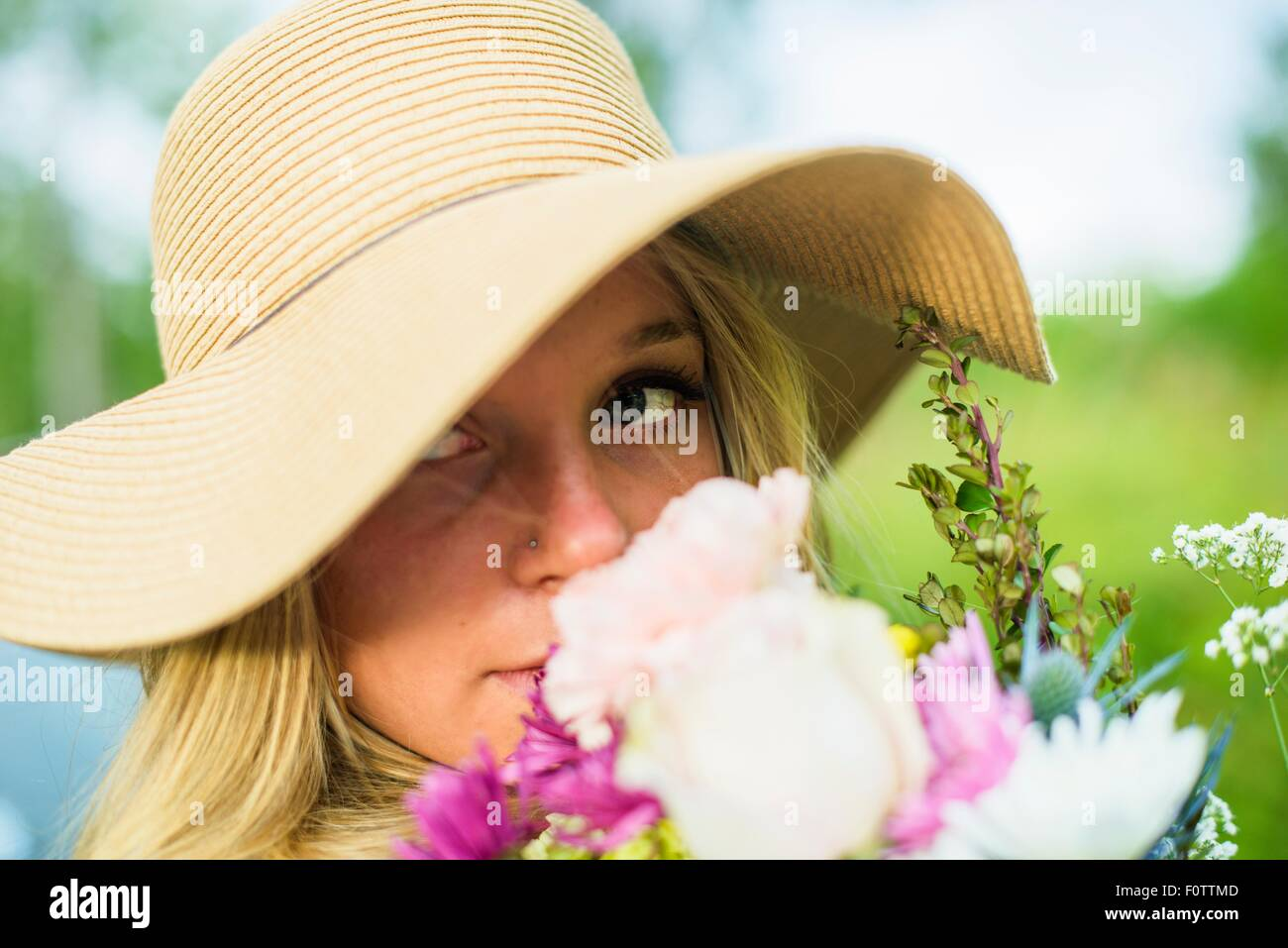 Close up portrait of young woman with bunch of flowers and wearing straw hat - Stock Image
