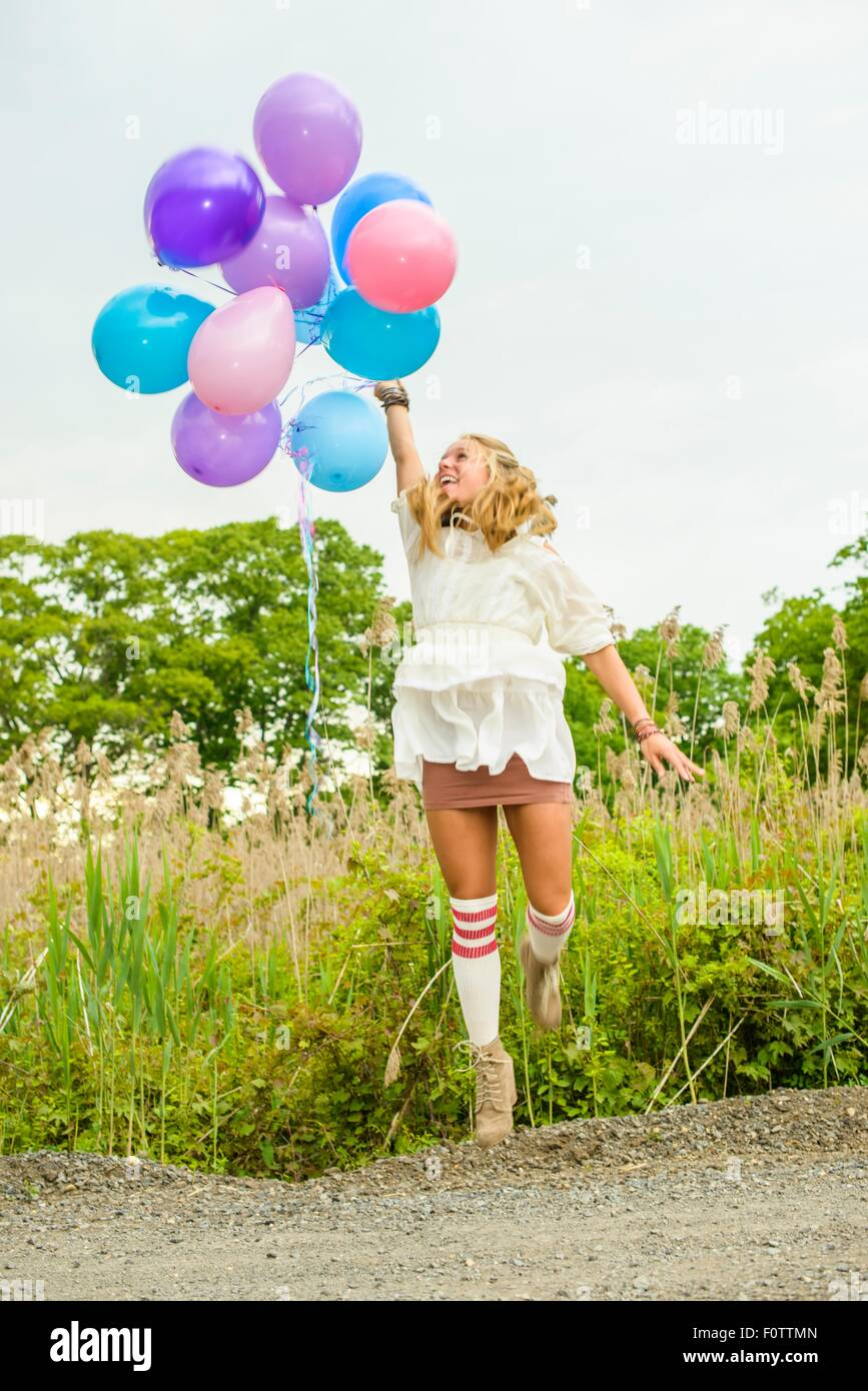 Young woman jumping with bunch of balloons on rural road - Stock Image