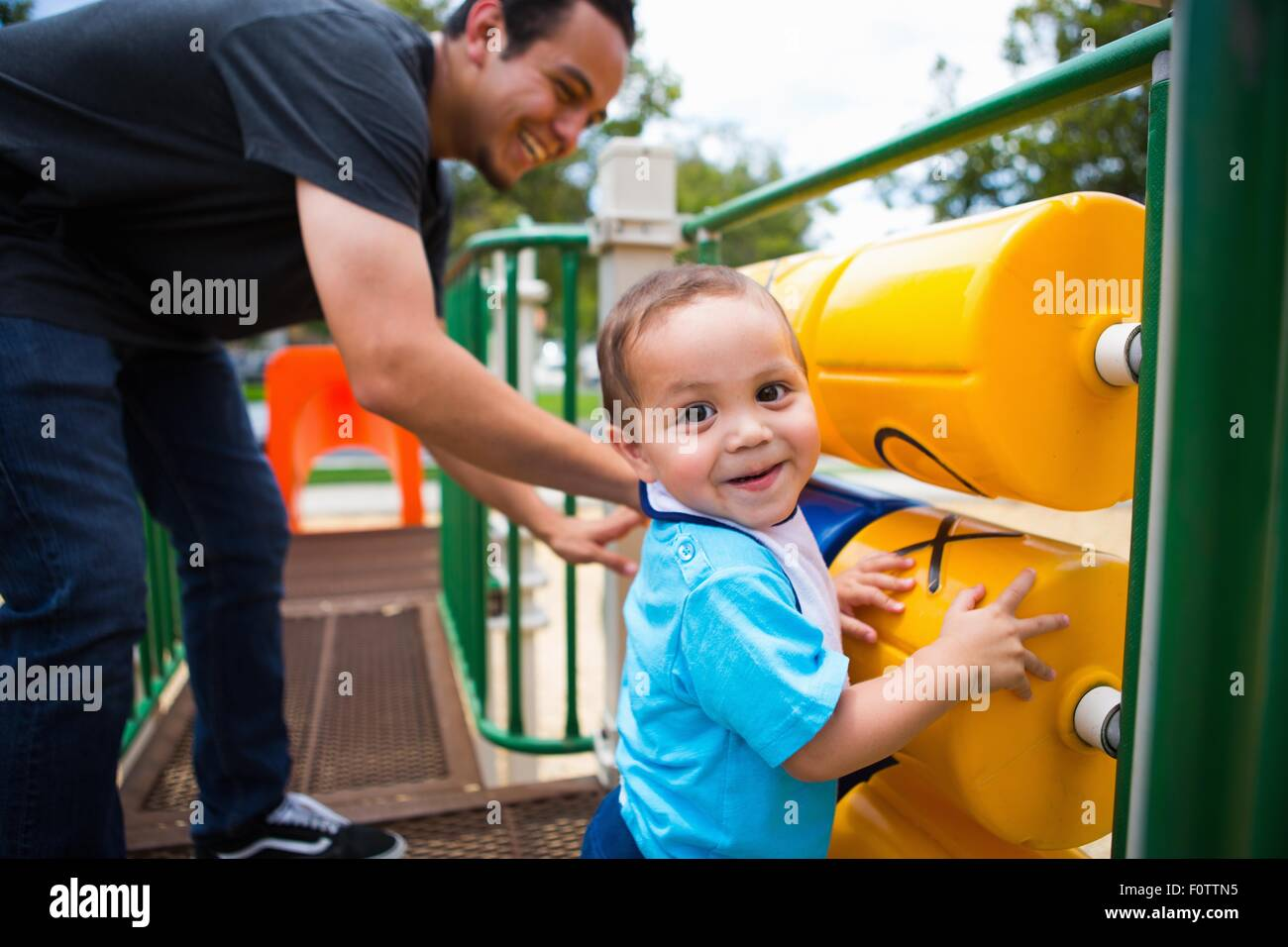 Young man playing with toddler brother on playground equipment - Stock Image