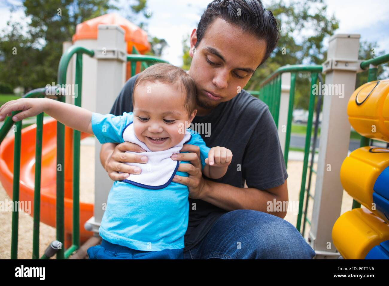 Young man guiding toddler brother on playground slide - Stock Image
