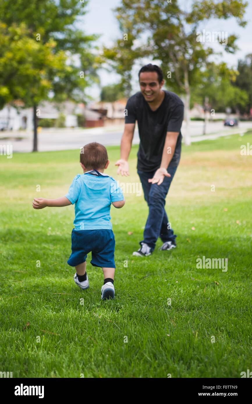 Young man playing with toddler brother in park - Stock Image
