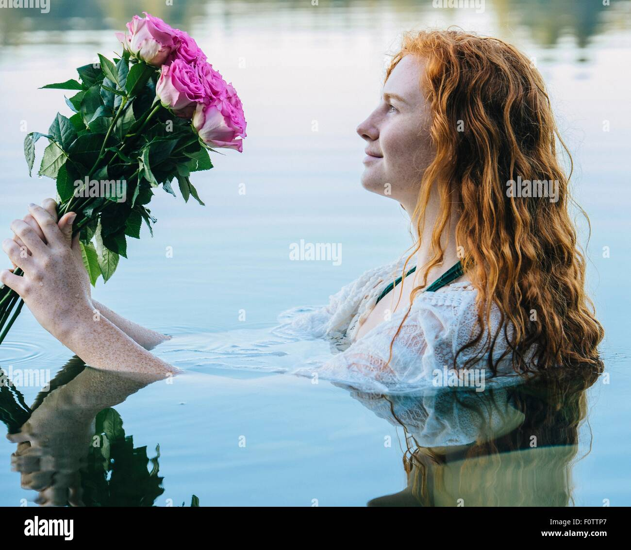 Head and shoulders of young woman with long red hair in lake gazing at bunch of pink roses - Stock Image