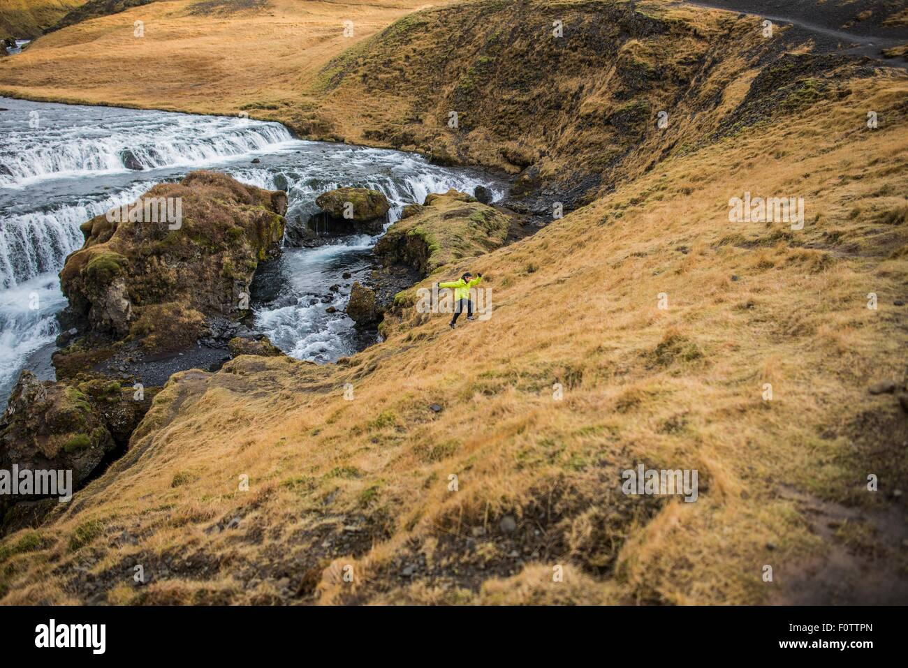 Male tourist running up hill at Skogafoss, Iceland - Stock Image