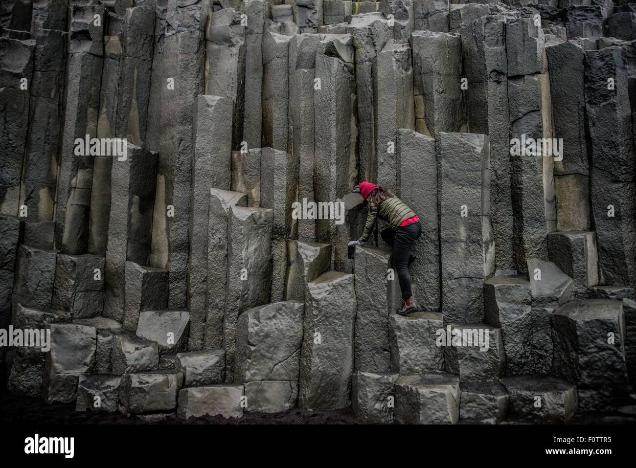 Female tourist climbing up rock formation,  Reynisfjara, Iceland - Stock Image