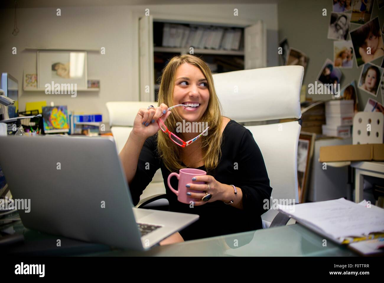 Young woman in office, sitting at desk, holding eyeglasses and coffee - Stock Image