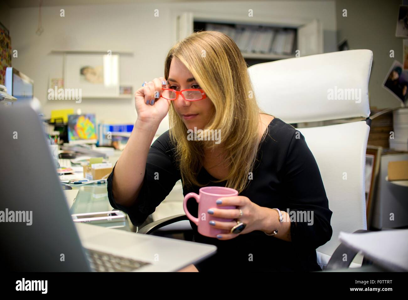 Young woman in office, sitting at desk, holding coffee cup, putting on glasses - Stock Image