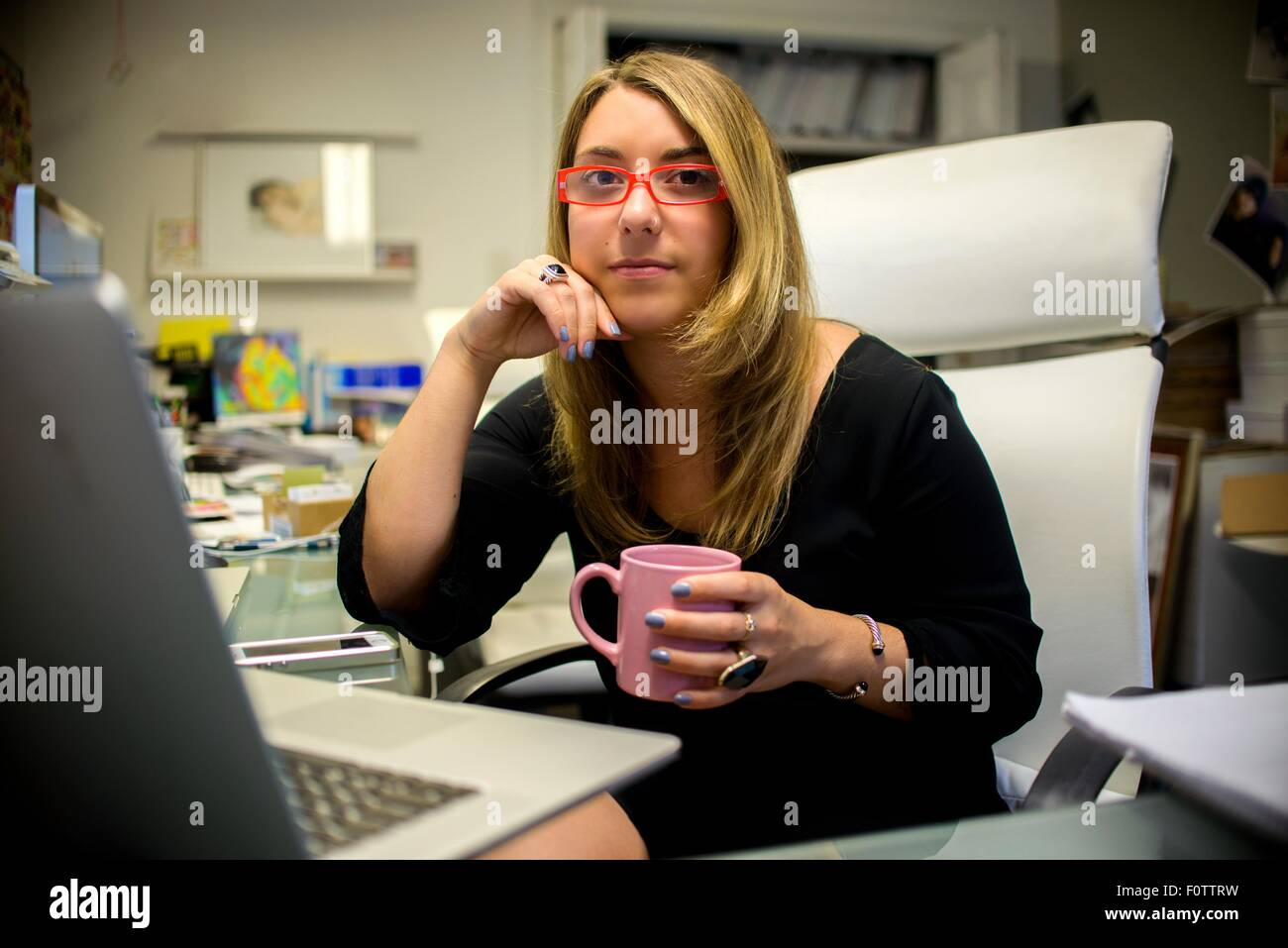 Portrait of young woman in office, sitting at desk, holding coffee cup - Stock Image