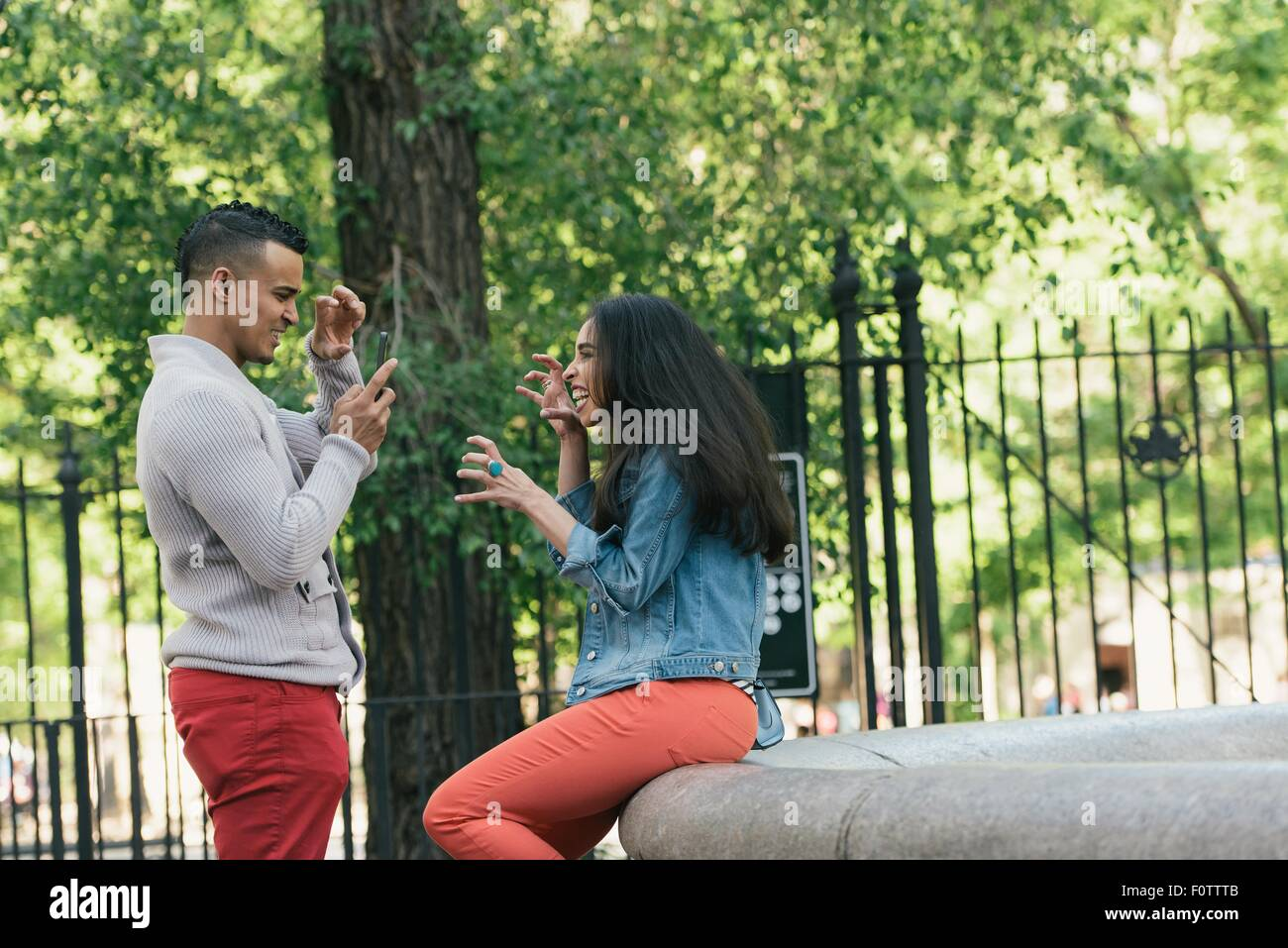 Mid adult man taking smartphone photograph of girlfriend in city park - Stock Image