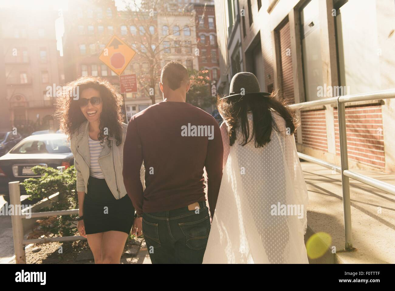 Portrait of three mid adult  friends back and front on city street - Stock Image