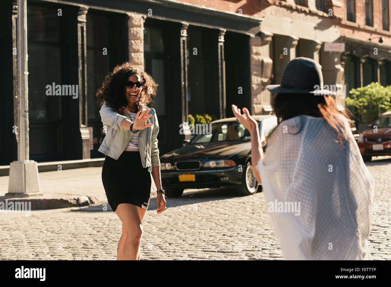 Two mid adult female friends greeting each other on city street - Stock Image