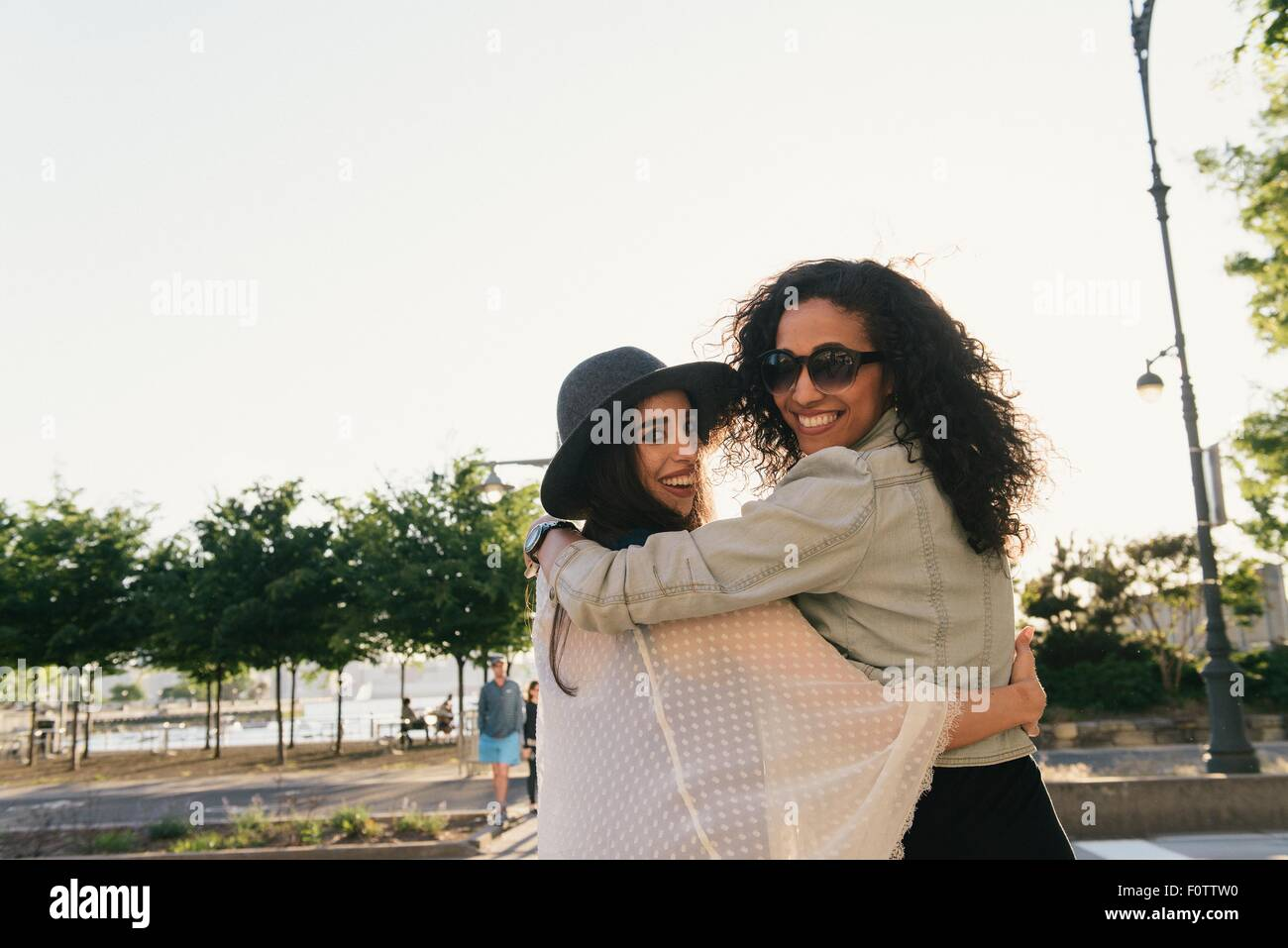 Portrait of two female mid adult friends looking over their shoulder  on waterfront - Stock Image