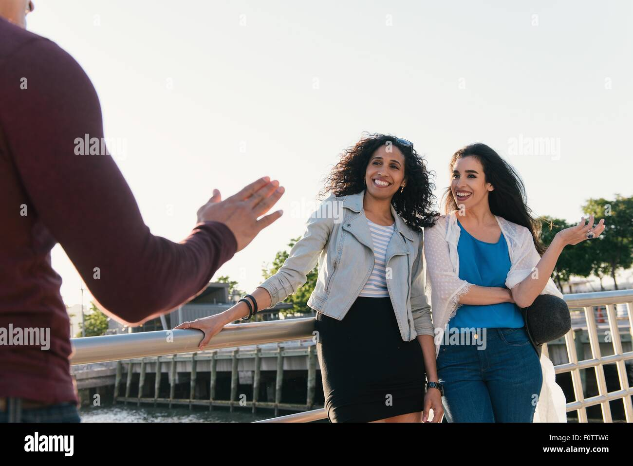 Two mid adult women greeting male friend on waterfront - Stock Image
