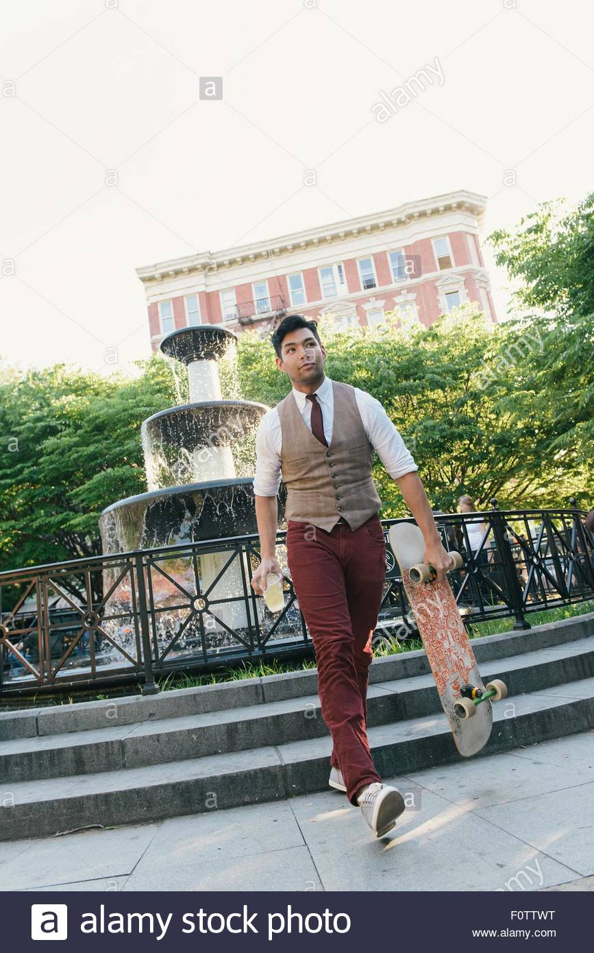 Stylish mid adult man walking in park with skateboard, West Village, Manhattan, USA - Stock Image