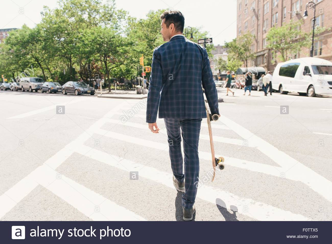 Rear view of suit wearing male skateboarder crossing road, West Village, Manhattan, USA - Stock Image